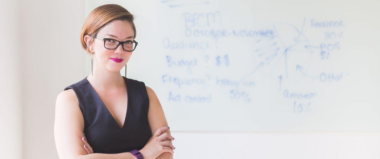 XUNDWORKEN Home - Arbeiten mit mehr Zufriedenheit - Frau steht selbstbewusst vor Whiteboard
