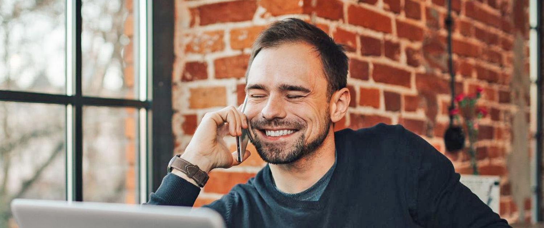 XUNDWORKEN Home - Arbeiten mit mehr Zufriedenheit - Mann freut sich beim telefonieren
